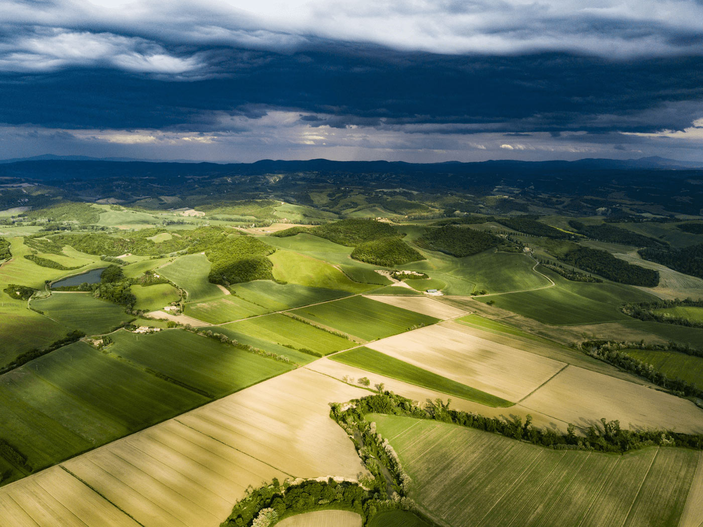 Green wide perspective from above with a cloudy dark blue sky